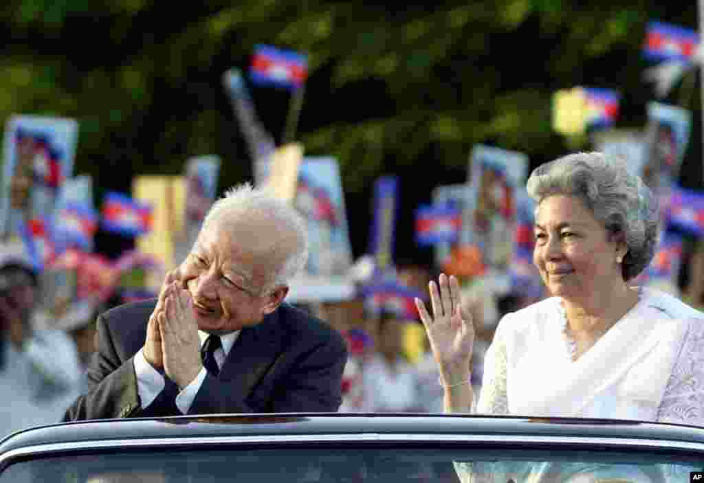 Then King Sihanouk and Queen Moniquegreet well-wishers from a limousine after a ceremony ending three official days celebrating Cambodia's 50 years of Independence in capital Phnom Penh, November 11, 2003.