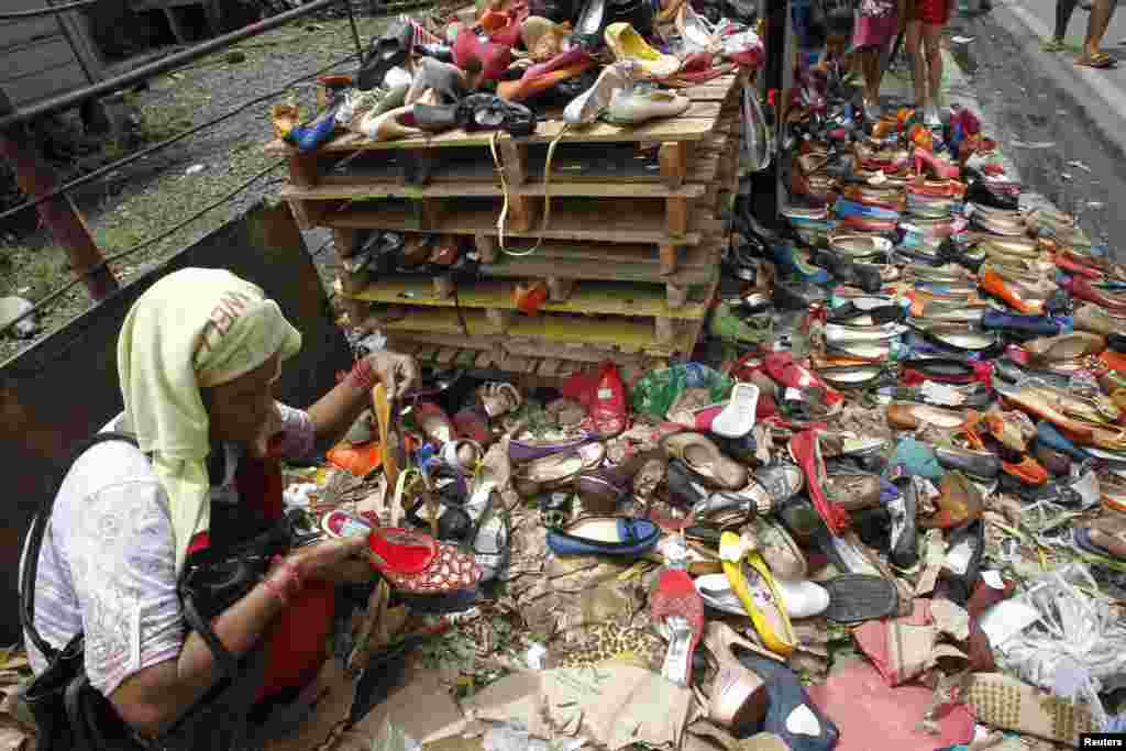 A woman looks at flood-damaged ladies footwear on sale for 10 pesos (22 cents) a pair at a slum area in Manila, Philippines.