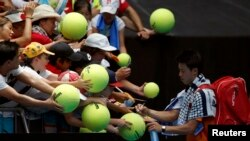 Japan's Kei Nishikori signs autographs after winning his first round match against Germany's Philipp Kohlschreiber at the Australian Open tennis tournament at Melbourne Park, Australia, January 18, 2016.