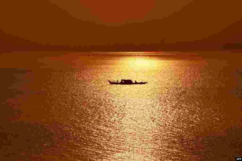 A fishing boat travels along the Mekong River as the sun rises over Phnom Penh, Cambodia.