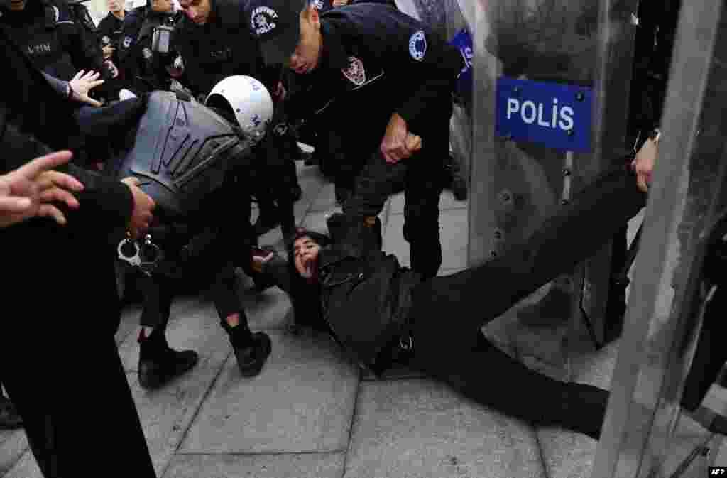 10일 터키 이스탄불 경찰들이 법원 앞에서 한 사회운동가를 진압하고 있다. 이 여성은 수 개월간 투옥 중인 한 학생운동가의 선거 공판에 참석하려 했으나 저지당했다.