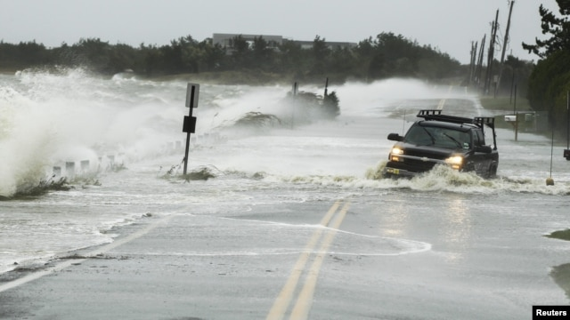 A truck drives through water pushed over a road by Hurricane Sandy in Southampton, New York, October 29, 2012.