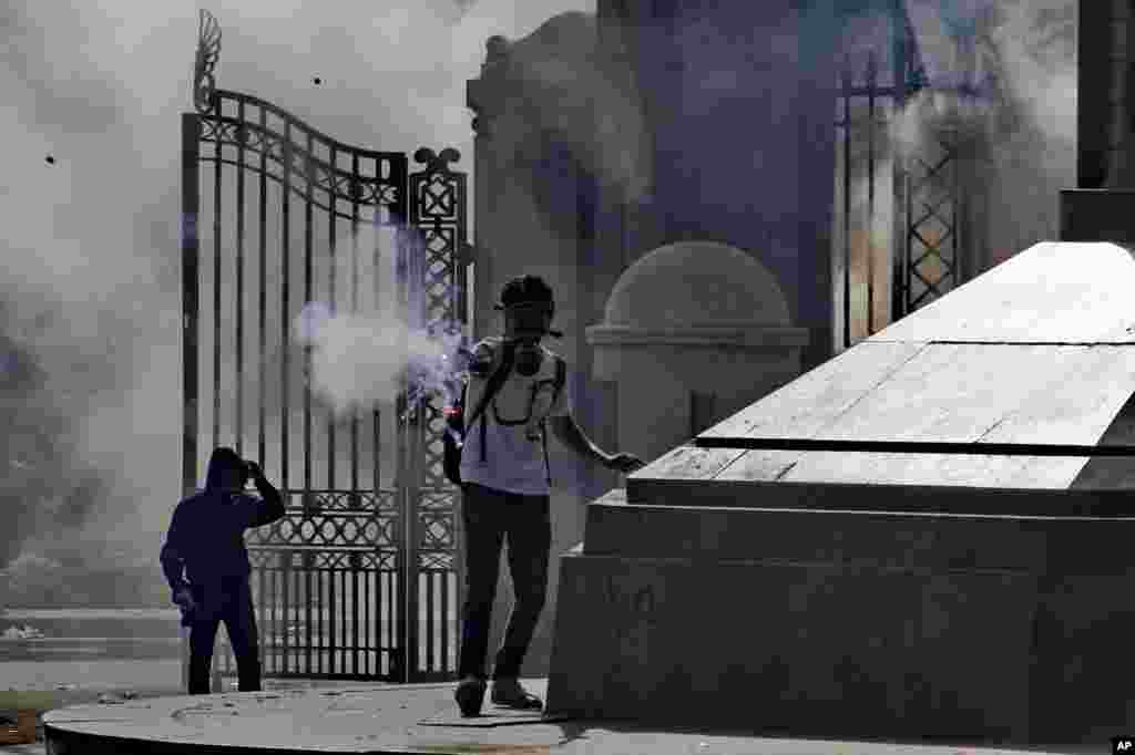 A protester fires a flare during clashes with security forces outside of Cairo University in Giza, March 26, 2014.