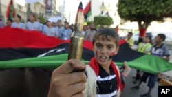 A boy holds a bullet while attending a rally where protesters were calling on the International Criminal Court to issue arrest warrants for Libyan leader Moammar Gadhafi, near the courthouse in Benghazi, Libya, May 14, 2011