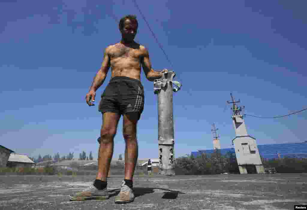 A man shows the remains of a military projectile in the village of Spartak outside Donetsk, Sept. 3, 2014.