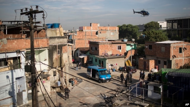 A military police helicopter flies over the Mandela shantytown, part of the Manguinhos slum complex, as policemen patrol the area on the ground after attacks to their Pacifying Police Unit post in Rio de Janeiro, March 21, 2014.