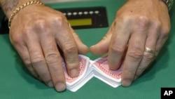 A man shuffles cards before he deals a poker game