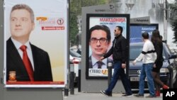 """Young people pass beside boards with election posters of Gjorge Ivanov, (l), current Macedonian President and a candidate of the ruling conservative VMRO-DPMNE party, with a slogan """"The State Before All"""", and Stevo Pendarovski, (c), a candidate of opposition Social-democrats, with a slogan """"Macedonia Deserves a President"""", in Skopje, Macedonia."""