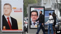 Young people pass beside boards with election posters of Gjorge Ivanov, left, current Macedonian President and a candidate of the ruling conservative VMRO-DPMNE party.