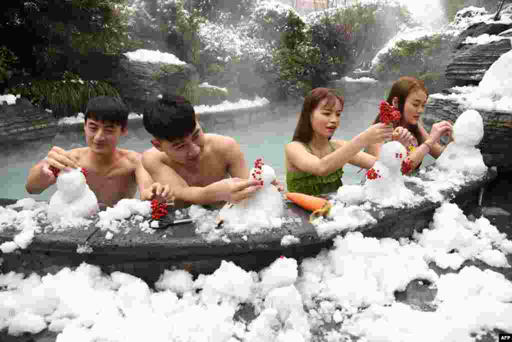 Visitors make snowmen beside a pool at a hot spring in Hangzhou, in China's eastern Zhejiang province.