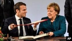 Presiden Perancis Emmanuel Macron (kiri) dan Kanselir Jerman Angela Merkel menandatangani pakta persahabatan baru untuk mempererat aliansi kedua negara, di Aachen, Jerman Selasa (22/1).