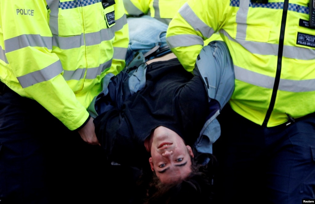 Police detain a protester as climate change activists demonstrate during an Extinction Rebellion protest at the Waterloo Bridge in London, Britain, April 15, 2019.
