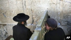 An ultra-Orthodox Jewish man and woman pray on either side of a fence at the Western Wall, the holiest site where Jews can pray, in Jerusalem's Old City, 15 Dec 2010