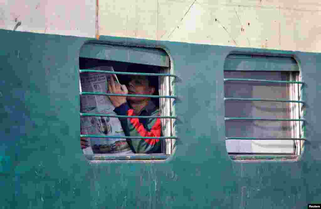 A man reads a newspaper on an intercity train in New Delhi, India.