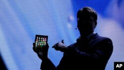 SJustin Denison, SVP of Mobile Product Development, shows off the Infinity Flex Display of a folding smartphone during the keynote address of the Samsung Developer Conference Wednesday, Nov. 7, 2018, in San Francisco. (AP Photo/Eric Risberg)