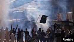 بھارت کے زیرِ انتظام کشمیر میں مظاہرین پاکستان کا پرچم لہرا رہے ہیں۔ (فائل فوٹو)