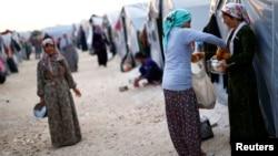 Người Kurd từ thành phố Kobani ở Syria, tại một trại tị nạn ở thị trấn Suruc, tỉnh Sanilurfa chia nhau thực phẩm, 17/10/14