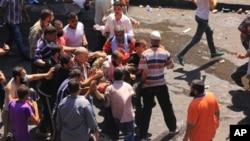 Para pendukung presiden Mesir terguling Mohamed Morsi membawa kawan mereka yang terluka akibat bentrokan dengan pasukan keamanan (14/8). (AP/Mohammed Abu Zeid)