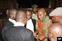 FILE - Biafran separatist leader Nnamdi Kanu, center right, speaks to his lawyers at the Federal High court in Abuja, Nigeria, Jan. 29, 2016. Kanu's current whereabouts are unknown.