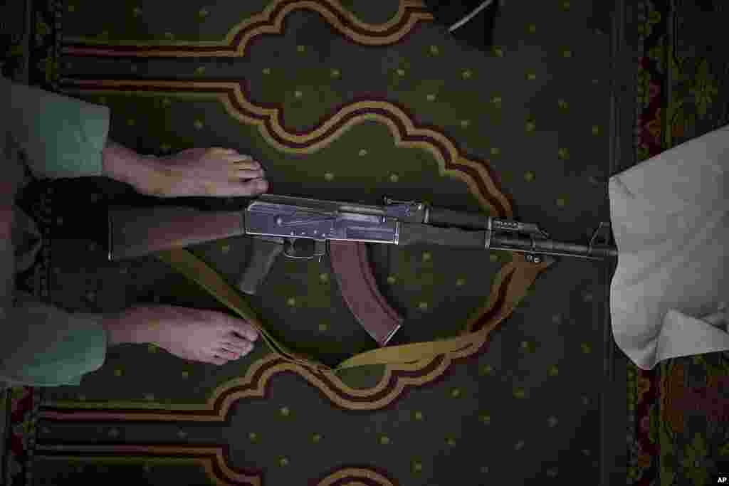 A Taliban fighter lays his AK-47 rifle down during Friday prayers at a Mosque in Kabul, Afghanistan.