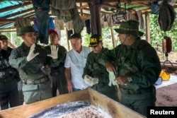 Venezuela's Defense Minister Vladimir Padrino (front L) speaks during a military operation to destroy a clandestine drug laboratory, near of the border with Colombia, in the state of Zulia, Dec. 6, 2014.