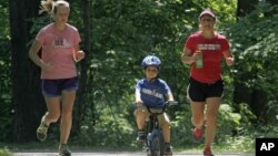 In this 2012 file photo, Andrea Lemastra, right, and Kim Walsh, left, jog on a wooded park trail with Lemastra's four-year-old son, Luca, in the U.S. state of Ohio. (AP Photo/Mark Duncan)