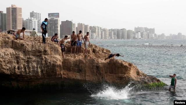 Youths jump into the sea to cool off on a hot day in the Egyptian coastal city of Alexandria May 24, 2013.