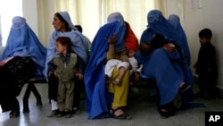 Afghan women clad in burqas sit with their children, at the Indira Ghandi Children's Hospital in Kabul Afghanistan.