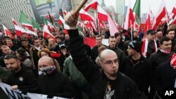 Right-wing protesters wave flags at the start of the Independence Day march organized by nationalist parties, in Warsaw, Poland, Nov. 11, 2014.