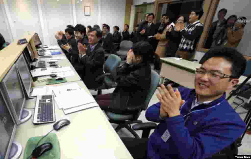 31일 나로과학위성과 교신에 성공하고 나서 환호하는 한국 카이스트 인공위성센터 관계자들.