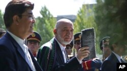 阿富汗總統卡爾扎伊在喀布爾總統府28日的開齋節祈禱後離開現場