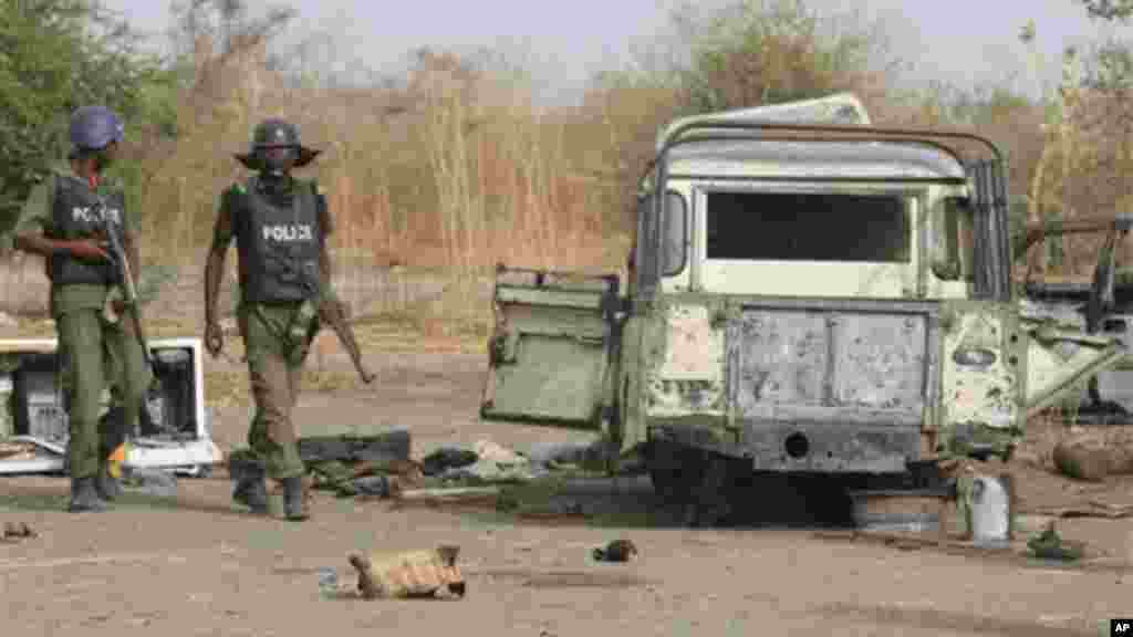 Police officers walk past the remains of a truck at a former Islamic extremist camp near Marte, Nigeria.