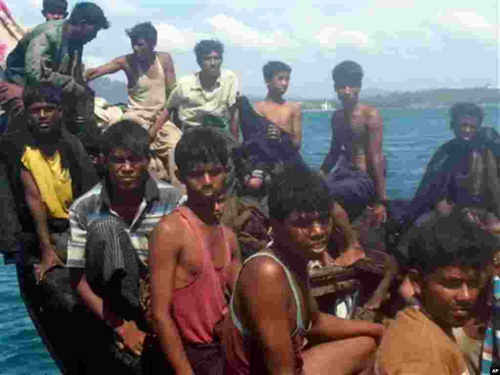 In this photo taken Jan.1, 2013, Rohingya refugees sit in a boat as they are intercepted by Thai authorities off the sea in Phuket, southern Thailand. Officials said the 73 refugees from Myanmar's Rohingya minority found adrift off a Thai resort island w