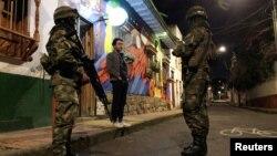 Seorang warga berbicara dengan dua tentara yang melakukan tugas patroli penerapan jam malam di Candelaria, Bogota, Jumat (22/11).