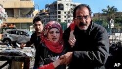레바논 베이루트의 쿠웨이트 문화원 인근에서 19일 폭탄 테러가 발생한 가운데 한 남성이 다친 여성을 돕고 있다.