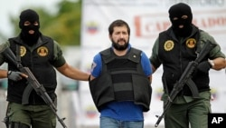 "FILE - Daniel Barrera , one of Colombia's most wanted drug lords, whose alias is ""El Loco"" is escorted in a flak jacket by National Guard troopers as he is deported to Colombia from Venezuela, Nov. 14, 2012."