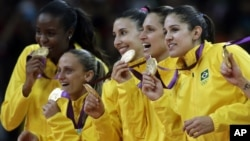 Members of the Brazil women's volleyball team show off their gold medals following a 3-1 win over the United States during the women's gold medal volleyball match at the 2012 Summer Olympics, Saturday, Aug. 11, 2012, in London.