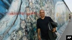 کانی علوی، هنرمند ایرانی مقیم آلمان در مقابل نقاشی دیواری خود روی بخشی از دیوار برلین