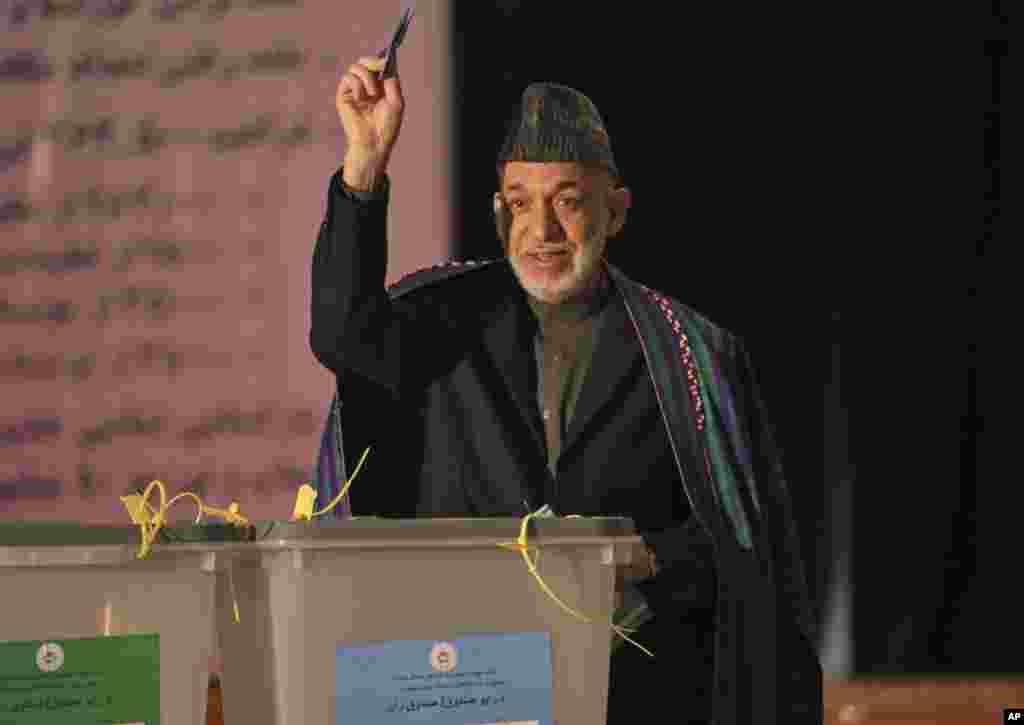 Afghan President Hamid Karzai shows his ballot paper to the media before he casts his vote at Amani high school, near presidential palace in Kabul, April 5, 2014.