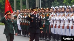 U.S. Chairman of the Joint Chiefs of Staff General Martin Dempsey (C) reviews the guard of honor with his Vietnamese counterpart General Do Ba Ty during a welcoming ceremony at Vietnam's Defense Ministry in Hanoi, Aug. 14, 2014.