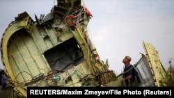 22 ივლისი, 2014 წელი, ინსპექტორები თვითმფრინავის კატასტროფის ადგილს ამოწმებენ.