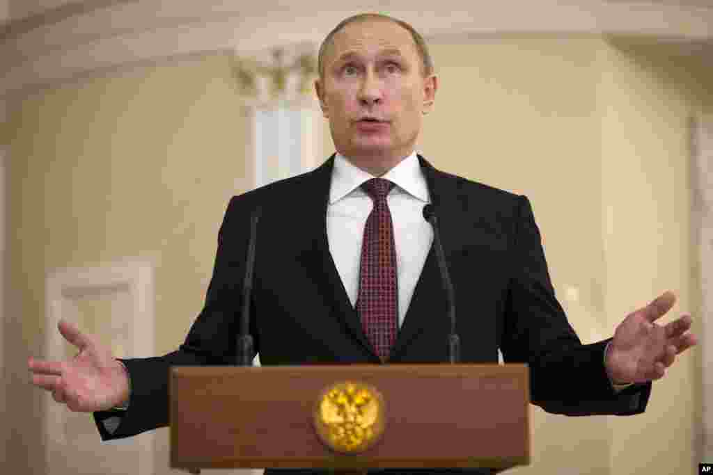 Russian President Vladimir Putin gestures as he speaks to the media after the peace talks in Minsk, Belarus, Thursday, Feb. 12, 2015.