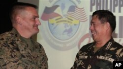Direktur Pelatihan Program Balikatan 2012 Amerika, Brigjen Marinir Frederick Padilla (kiri) berjabat tangan dengan Pimpinan Militer Filipina, Jendral Jesse Dellosa dalam pembukaan latihan bersama tahunan di Camp Aguinaldo, Filipina (16/4).