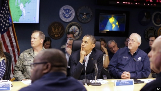 President Barack Obama, center, attends a briefing with Federal Emergency Management Agency administrator Craig Fugate, right, at the National Response Coordination Center at FEMA Headquarters in Washington, on Sunday, Oct. 28, 2012.