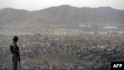 Афганский полицейский смотрит на Кабул.