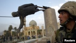 A U.S. soldier watches as a statue of Iraq's President Saddam Hussein falls in central Baghdad in this photo dated April 9, 2003.