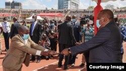 Rais wa Kenya Uhuru Kenyatta (Kulia) amkabidhi tuzo Mkenya mmoja ambaye hakutambulishwa wakati wa maadhimisho ya miaka 57 tangu nchi hiyo kupata uhuru kutoka kwa Uingereza.