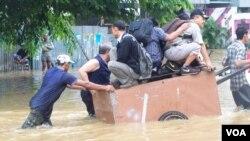 Masyarakat mengungsi dari banjir dengan menggunakan gerobak (13/1). (VOA/Iris Gera)
