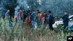 Illegal migrants are seen at the railway crossing at the border between Hungary and Serbia near Roszke, 180 kms southeast from Budapest, Hungary, Aug. 25, 2015.