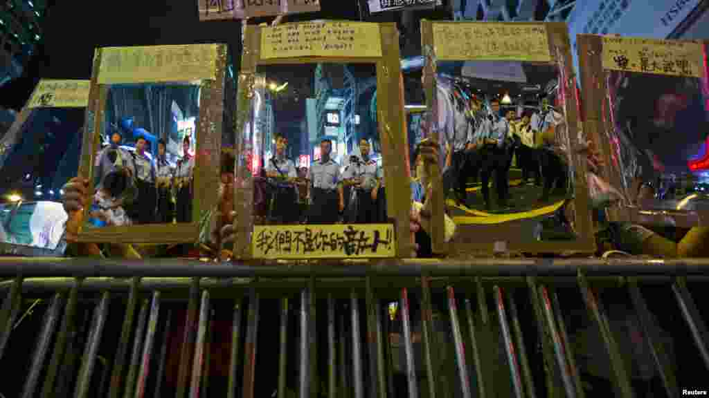 Police officers are reflected on reflective materials held by a pro-democracy protesters on a blocked road at Mongkok shopping district in Hong Kong, Oct. 19, 2014.